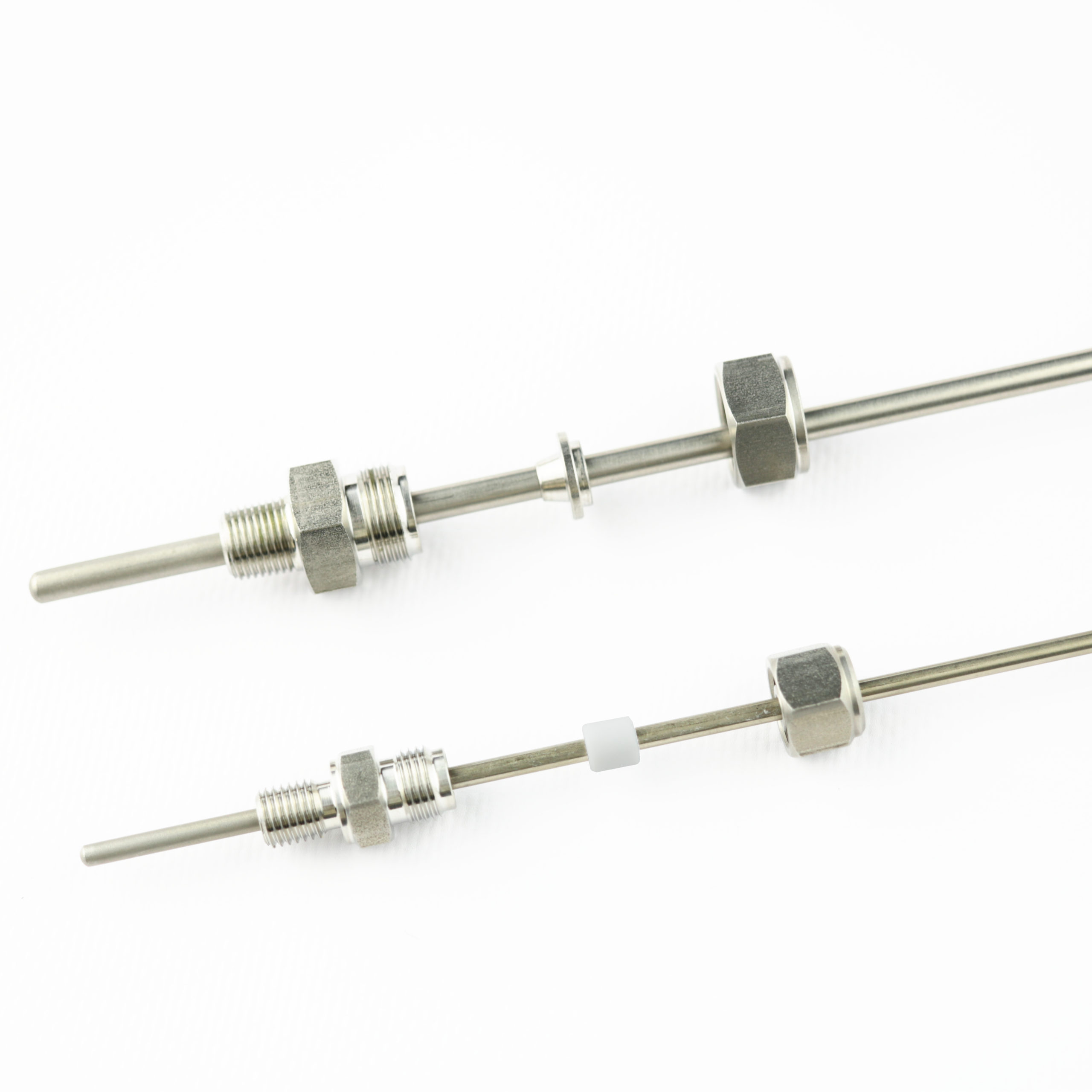 Two compression fittings next to each other. One with a metallic and one with a plastic ferrule or compression ring.
